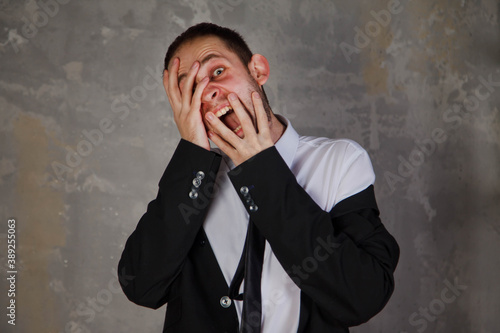 Emotional young man in suit depicts horror and fear on gray textured background Wallpaper Mural