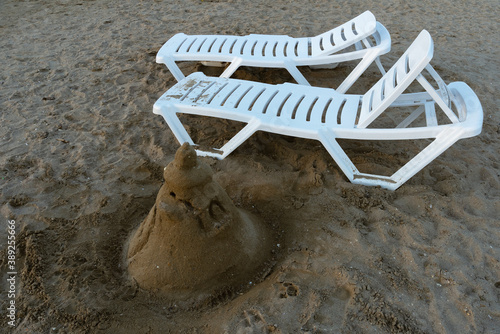 Fotografie, Obraz Two empty beach loungers on the evening beach and a sand castle, gray sand, befo