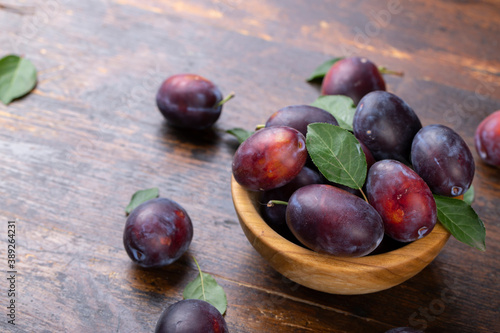 Fototapeta Fresh plums with leaves in a wooden bowl on a brown table.