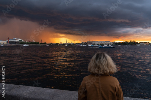 Fotografia Woman looking at the approaching thunderstorm in the city standing on embankment of Neva river in St