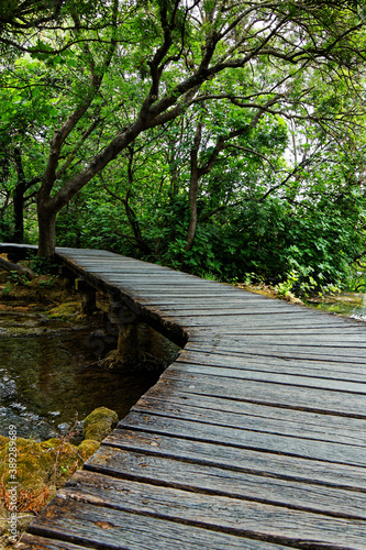 Canvastavla view on an old wood footbridge crossing a river in the forest