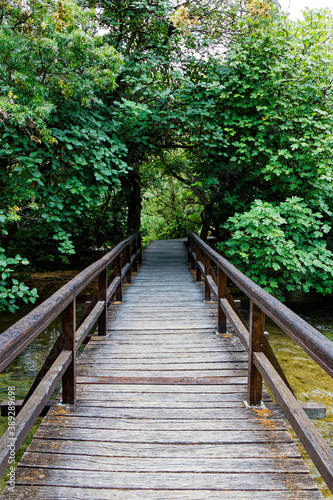 view on an old wood footbridge crossing a river in the forest Fototapet