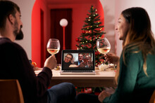 Couple Celebrating Christmas In Quarantine Due To Covid 19, Making A Video Call To Parents And In-laws. New Normal In Times Of Coronavirus.