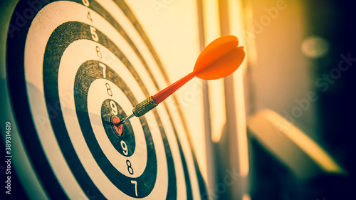 Fototapeta Bulls eye or dart board has red dart arrow throw hitting the center of a shooting target for business targeting and winning goals business concepts