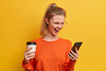Irritated Emotional Woman Uses Modern Technologies Screams Loudly And Concentrated In Smartphone Display Reads Something Annoying Drinks Aromatic Beverage From Paper Cup Isolaed Over Yellow Wall