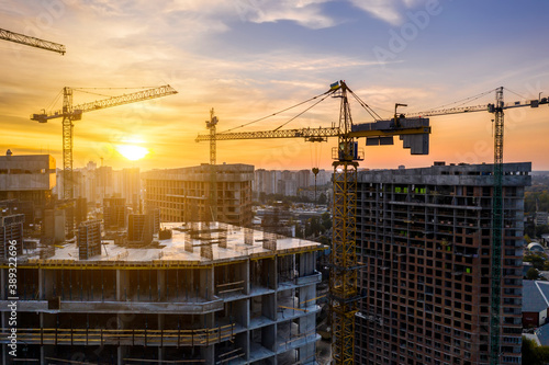 Construction site with cranes at sunset Fototapet
