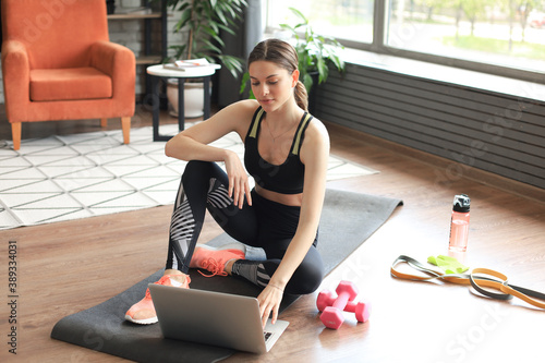 Obraz Beautiful slim sporty woman in sportswear is sitting on the floor with dumbbells and bottle of water and is using a laptop at home in the living room. Healthy lifestyle. Stay at home activities. - fototapety do salonu