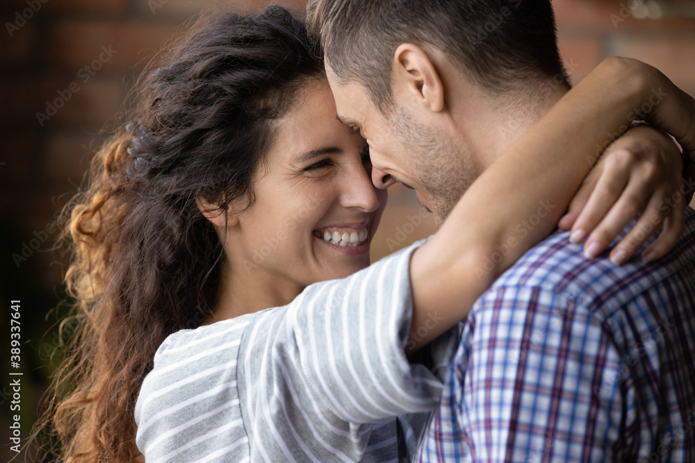 Fototapeta Close up of happy young Caucasian couple hug and cuddle enjoy tender close romantic moment together. Smiling millennial man and woman embrace show love and care in relationship. Marriage concept.