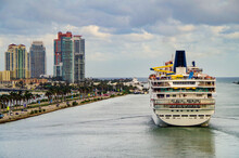 Luxury Modern Cruiseship Or Cruise Ship Liner Departing Port Of Miami With South Beach Hotel Resort Skyline And Marina With Motor And Sailing Boats And Yachts And McArthur Causeway