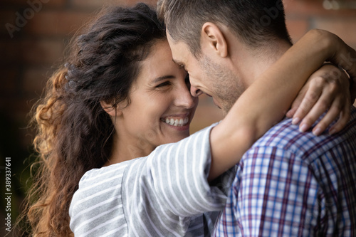 Close up of happy young Caucasian couple hug and cuddle enjoy tender close romantic moment together Canvas
