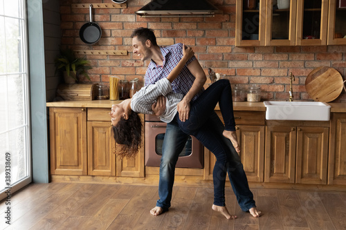 Carta da parati Overjoyed Caucasian man and woman enjoy happy leisure weekend in new home dancing waltzing together