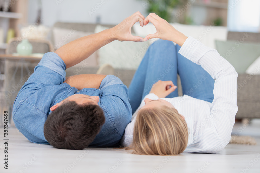 Fototapeta happy young couple sitting on floor at home
