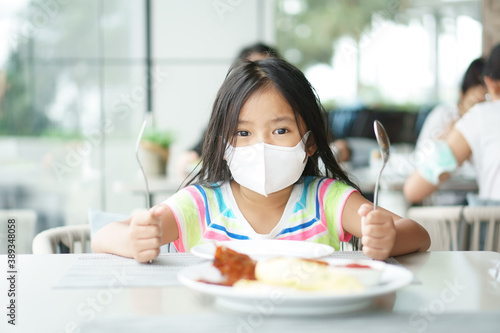 Foto Asian child or kid girl wearing white face mask to holding spoon and fork wait e
