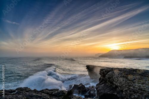 Fototapeta huge storm surge ocean waves crashing onto shore and cliffs at sunrise obraz