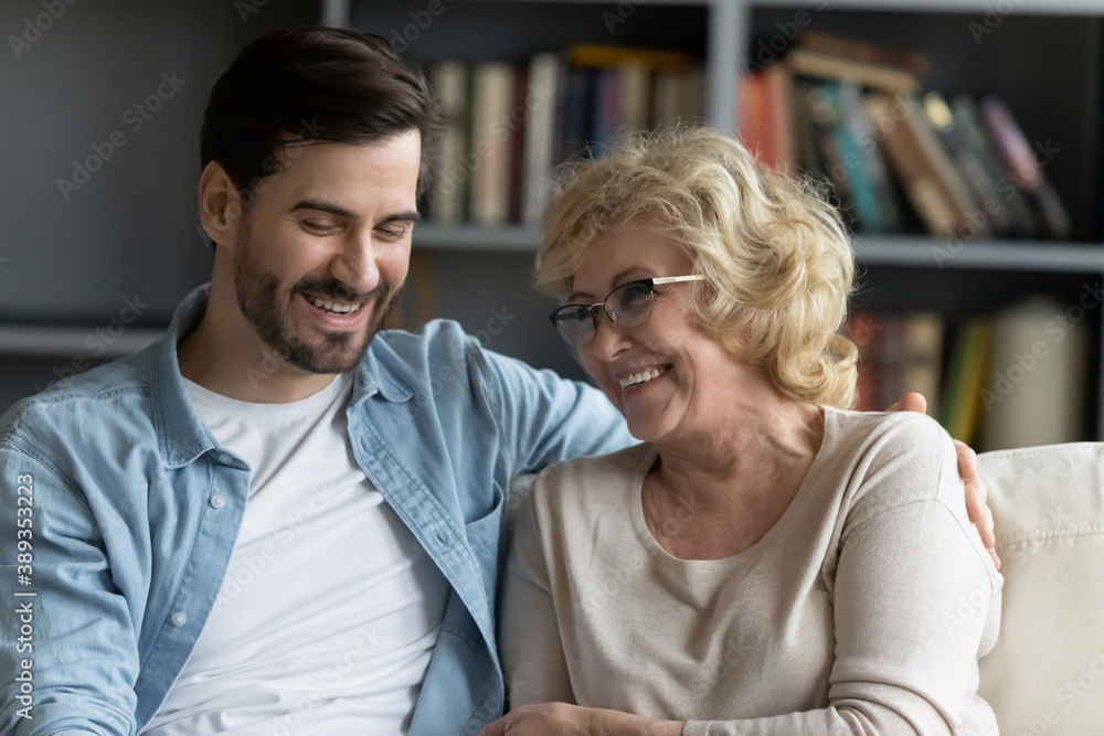 Fototapeta Head shot happy young bearded man embracing beautiful smiling middle aged senior mother in eyewear, relaxing together on comfortable sofa in living room, enjoying funny conversation or gossiping.