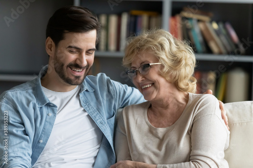 Photo Head shot happy young bearded man embracing beautiful smiling middle aged senior mother in eyewear, relaxing together on comfortable sofa in living room, enjoying funny conversation or gossiping