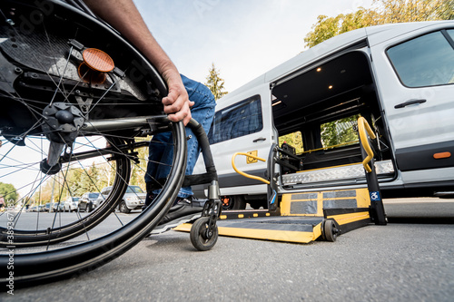 A man in a wheelchair moves to the lift of a specialized vehicle Poster Mural XXL