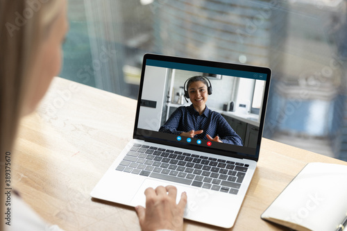 Fototapeta Close up rear view businesswoman chatting with Indian colleague online, using laptop and webcam, sitting at table in office, employees working together, brainstorming project, making video call obraz na płótnie