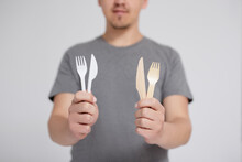 Zero Waste And Eco Friendly Concept - Man Comparing Plastic And Wooden Forks And Knives Over Grey Background