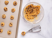 Overhead View Of Raw Cookie Dough In A Glass Bowl With A Baking Pan And Scooper