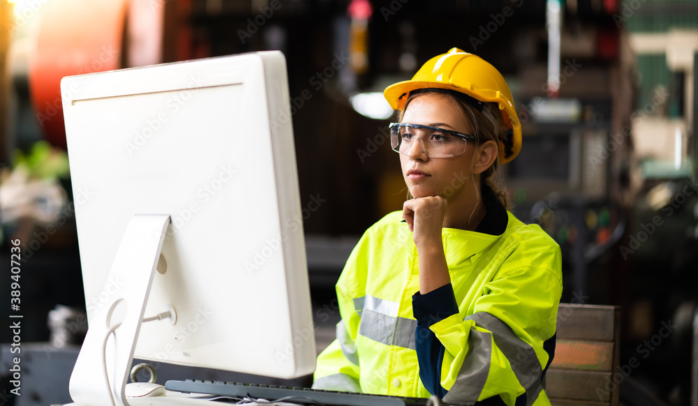 Fototapeta Female Quality control inspector checking workers at factory. Woman engineer with yellow hard hat helmet working on desktop computer inside factory
