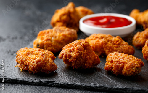 Spicy deep fried Chicken wings with ketchup on stone board Fototapet