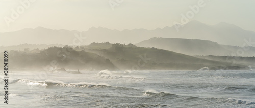 mountain landscape in silhouette with beach and waves breaking in the foreground
