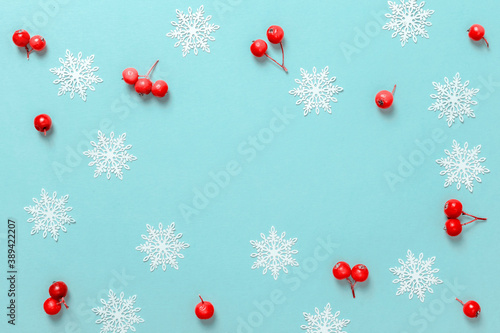Obraz Christmas pattern. White snowflakes, red berry in Christmas composition on pastel blue background for greeting card. Winter festive composition with copy space. - fototapety do salonu