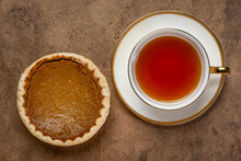 Cup Of Hot Tea And A Small Pumpkin Pie On A Textured Bark Paper, Thanksgiving And Fall Holidays Concept