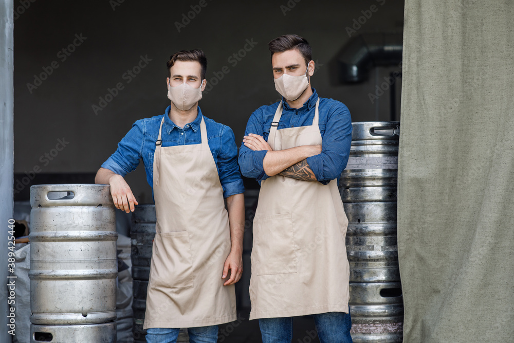 Fototapeta Two handsome men in aprons and protective masks stand in warehouse interior with metal barrels