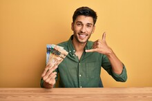 Young Handsome Man Holding Canadian Dollars Smiling Doing Phone Gesture With Hand And Fingers Like Talking On The Telephone. Communicating Concepts.