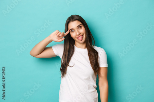 Image of funny cute girl in white t-shirt, mocking someone, pointing at head and Canvas