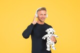 Happy infantile middle-aged man play with toy dog listening to music yellow background, headphones