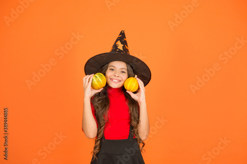 Happy girl on Halloween wear witch carnival costume indoor holding pumpkin, hall Fototapet