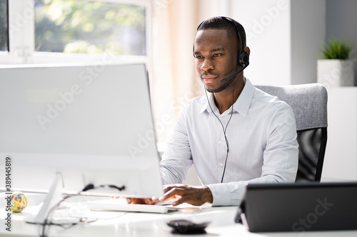 Obraz na plátně Business Service Agent With Headset At Computer