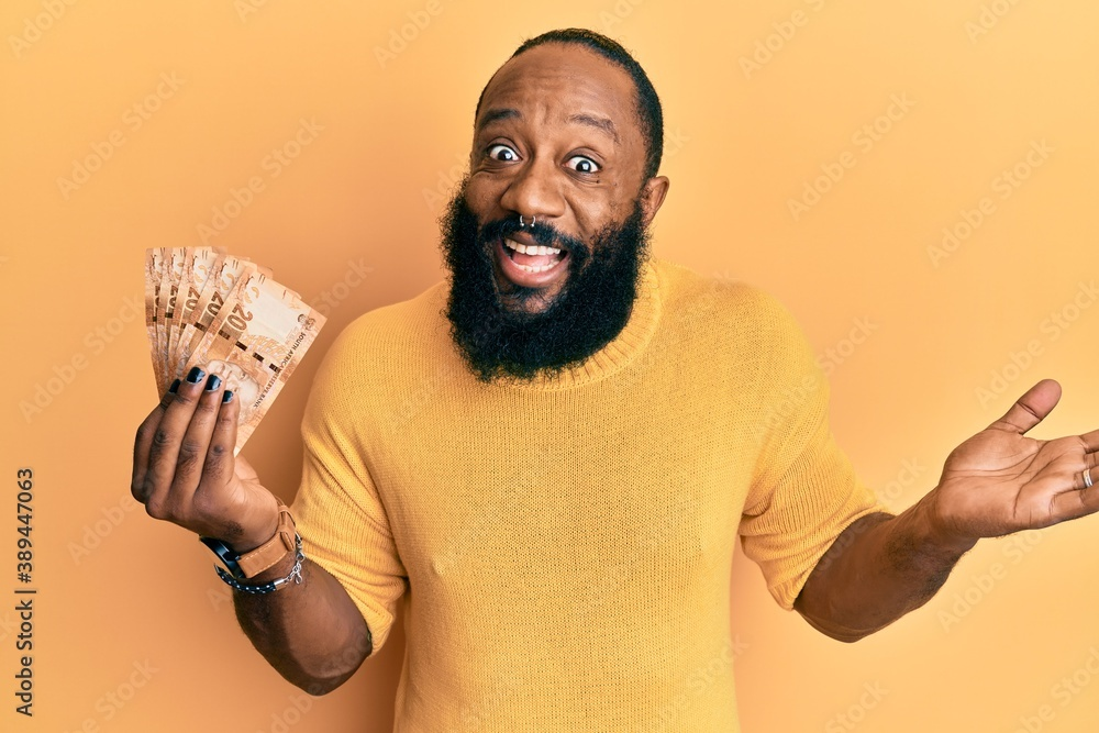 Fototapeta Young african american man holding south african 20 rand banknotes celebrating achievement with happy smile and winner expression with raised hand