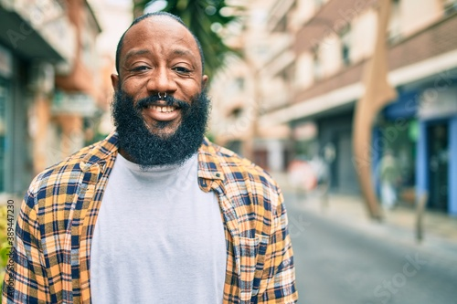 Obraz Handsome modern african american man with beard smiling positive standing at the street - fototapety do salonu