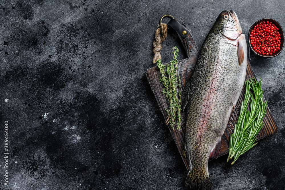 Fototapeta Raw Rainbow trout fish on a cutting board with herbs. Black background. Top view. Copy space