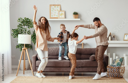Obraz happy family mother father and children dancing at home - fototapety do salonu