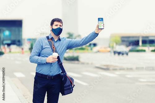 Man using mobile taxi app waiting cab or ride share with hand up Tableau sur Toile