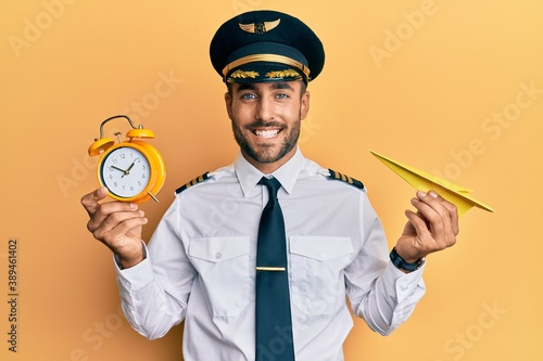 Vászonkép Handsome hispanic pilot man holding paper plane and alarm clock smiling with a happy and cool smile on face