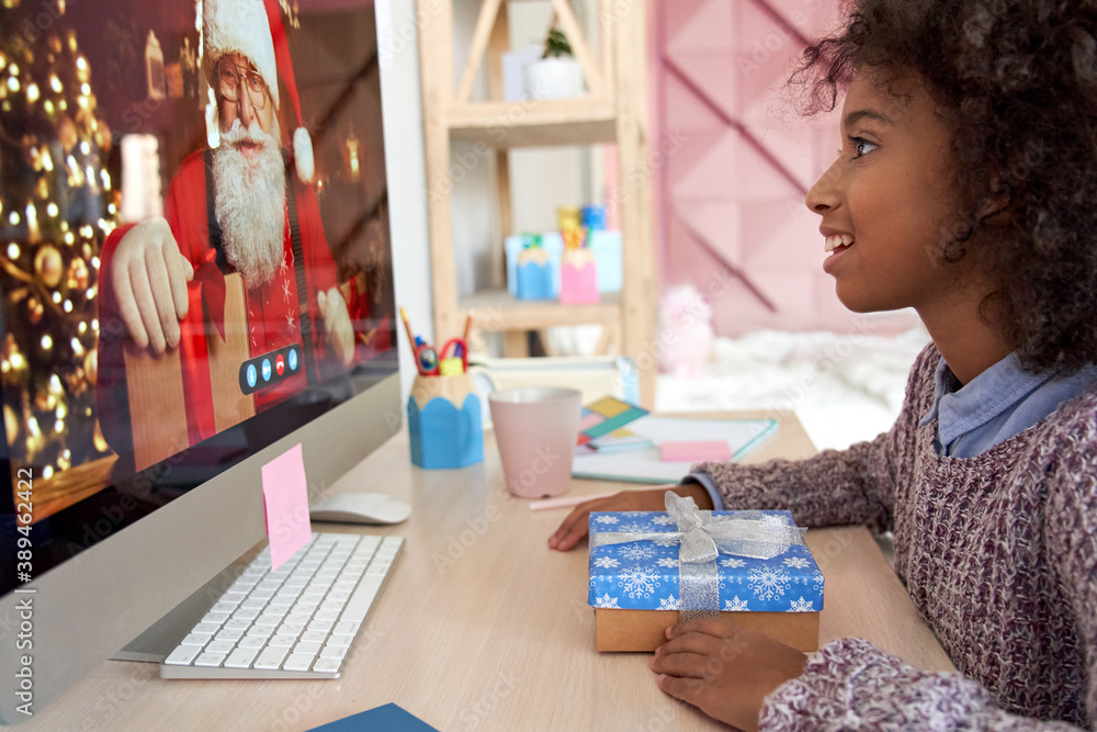 Fototapeta Happy african american kid girl talking to virtual santa claus saying New Year greetings to child on video conference online call chat using computer sitting at home table with Chrtistmas present.