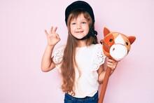 Little Caucasian Kid Girl With Long Hair Riding Horse Toy Wearing Vintage Helmet Doing Ok Sign With Fingers, Smiling Friendly Gesturing Excellent Symbol