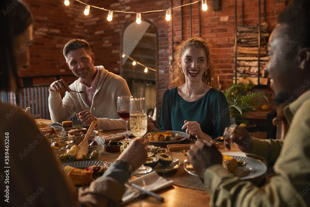 Fototapeta Group of cheerful adult people sitting at dinner table while enjoying party with outdoor lighting - obraz na płótnie