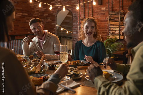 Photo Group of cheerful adult people sitting at dinner table while enjoying party with