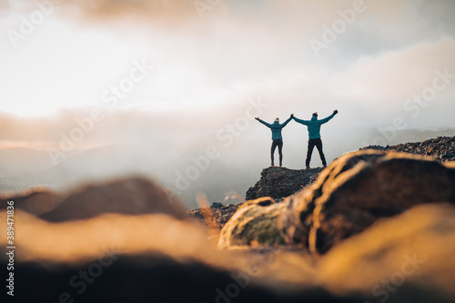 Obraz Couple travelers Man and Woman standing on cliff relaxing mountains and clouds aerial view Love and Travel happy emotions Lifestyle concept. Young family traveling active adventure vacations - fototapety do salonu