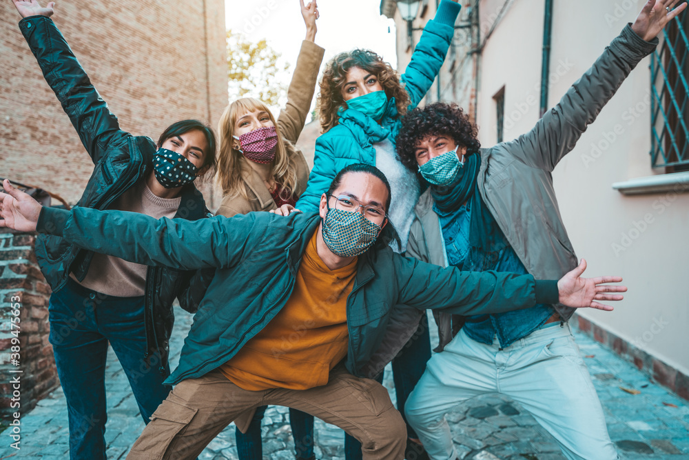 Fototapeta Happy friends walking on city street - New normal concept with young people having fun together covered by face masks
