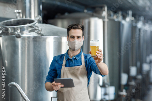 Confident specialist in apron holds beer glass, brewery expert controlling quality of ale