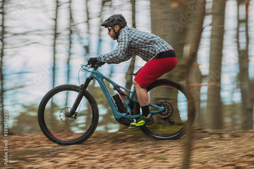 Fotomural Hipster biker charging downhill with a modern lightweight electric bicycle or mountain bike in autumn or winter setting in a forest
