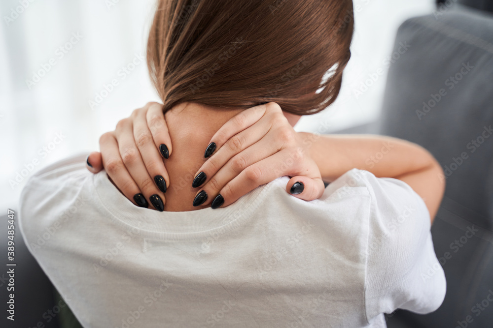Fototapeta Tired young woman touching stiff neck